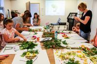 Pod okiem instruktor Katarzyny Brzezińskiej-Błaś uczestnicy warsztatów układali barwne kwiatowe wizerunki.